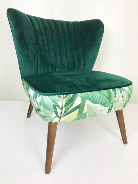 Green Velvet Winged Upholstered Occasional Chair With Tropical Background. Oak Coloured Wooden Legs